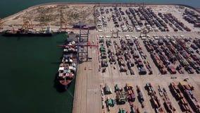 Área de carga industrial com o navio de recipiente na doca no porto, vista aérea filme