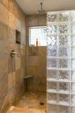 Área de la ducha del cuarto de baño del balneario con las paredes de la teja de piedra y del bloque de cristal en interior casero fotografía de archivo