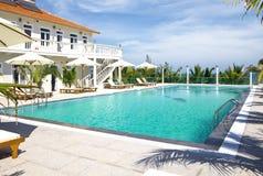 Área de la relajación con la piscina y los sunbeds Fotografía de archivo