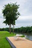 Área de la relajación con la tabla y la silla de madera en jardín Foto de archivo