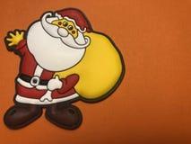 Área de mensaje vacío con la figura de la Navidad del padre como papel de nota o tablero de mensajes en fondo anaranjado Fotografía de archivo