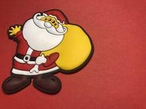 Área de mensaje vacío con la figura de la Navidad del padre como papel de nota o tablero de mensajes en fondo rojo Imagenes de archivo