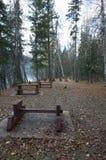 Área de picnic con las tablas junto a un lago Fotos de archivo libres de regalías
