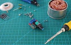 Área de trabalho eletrônica do reparo com a ferramenta na superfície de montagem verde imagens de stock royalty free
