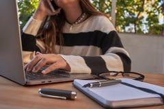 Área de trabalho portátil do escritório Escritório exterior com árvores Moça que fala no telefone e que trabalha com vidros do te imagem de stock royalty free