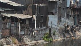 Área de tugurios en el riverbank en Jakarta indonesia metrajes