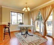 Área del comedor con las puertas y ventana y mesa redonda simple. Imagen de archivo libre de regalías