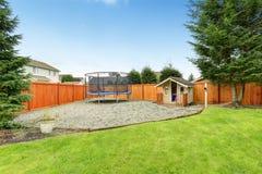 Área del patio trasero con el playghouse y el trumplin Imágenes de archivo libres de regalías