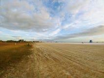 Área gramínea da praia sob um céu azul ensolarado brilhante com as nuvens macias brancas foto de stock royalty free
