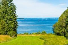 Área grande do gramado com árvores e fundo altos do mar e do céu azul Foto de Stock
