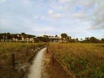 Área herbosa de la playa debajo de un cielo azul soleado brillante con las nubes mullidas blancas foto de archivo libre de regalías