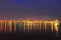 Área industrial por el agua en la noche Foto de archivo