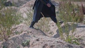 Área montanhosa do deserto As colisões pequenas são um homem em um casaco e em um chapéu pretos O sol está brilhando video estoque