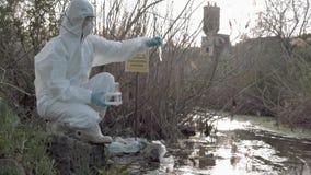 Área peligrosa, Hazmat en las batas protectoras que recogen la muestra infectada de agua para examinar en el lago contaminado con almacen de video