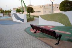 Área recubierta de goma del banco de parque de los niños Foto de archivo