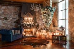 Árvore alternativa de cabeça para baixo no teto Decoração home do inverno Interior moderno do sótão com chaminé e parede de tijol fotografia de stock