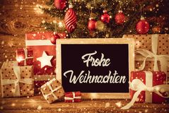 A árvore brilhante, presentes, caligrafia Frohe Weihnachten significa o Feliz Natal foto de stock