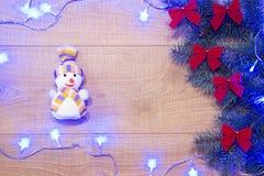 Árvore com curvas vermelhas, brinquedo de ano novo/Natal do boneco de neve, festão azul no molde de madeira do fundo Foto de Stock