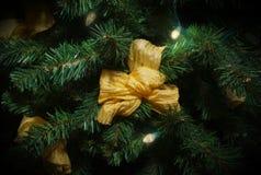 Árvore da decoração do Natal com luzes e a fita dourada do laço foto de stock