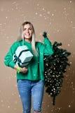 Árvore de abeto atrativa bonita do Natal da posse da mulher do cabelo louro com luzes e caixa de presente do bokeh na camiseta ve fotos de stock
