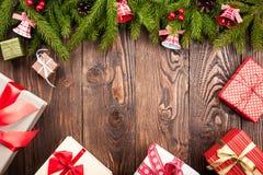 A árvore de abeto decorou sinos e caixas de presente no backgroun de madeira escuro Imagem de Stock Royalty Free