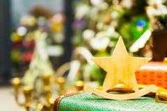 A árvore de abeto do Natal brinca a estrela que de madeira velha está em velas ardentes de uma mala de viagem retro, caixas, bola Foto de Stock