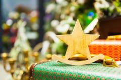 A árvore de abeto do Natal brinca a estrela que de madeira velha está em velas ardentes de uma mala de viagem retro, caixas, bola Fotos de Stock Royalty Free