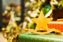 A árvore de abeto do Natal brinca a estrela que de madeira velha está em velas ardentes de uma mala de viagem retro, caixas, bola Fotografia de Stock Royalty Free