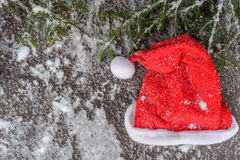 Árvore de abeto do Natal e chapéu vermelho em uma placa de madeira com neve, estrutura verde para chistmas Imagens de Stock