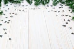 Árvore de abeto do Natal na neve com as estrelas de prata no fundo de madeira branco Fotografia de Stock Royalty Free