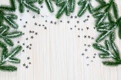Árvore de abeto do Natal na neve com as estrelas de prata no fundo de madeira branco Foto de Stock