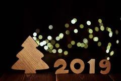 Árvore de abeto e texto de madeira 2019 da figura de madeira no fundo de madeira escuro com a festão da luz do diodo emissor de l fotografia de stock