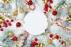 Árvore de abeto nevado, placa de papel redonda e decorações do Natal na opinião de tampo da mesa de madeira branca Configuração l fotografia de stock