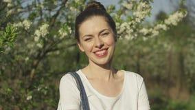 Árvore de florescência próxima de sorriso da mulher bonita video estoque