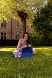 Árvore de grama de assento da mulher moreno, Groot Begijnhof, Lovaina, Bélgica fotos de stock royalty free