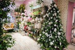A árvore de Natal é decorada com os brinquedos brancos e prateados na loja da decoração Fotos de Stock Royalty Free