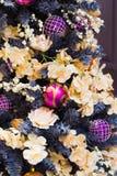 Árvore de Natal com as bolas luxuosas cor-de-rosa e violetas no fundo borrado na alameda Fim acima Teste padrão do Xmas imagem de stock royalty free