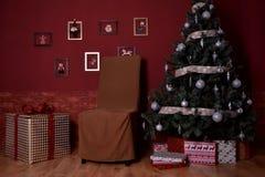 Árvore de Natal com brinquedos e a parede vermelha Fotos de Stock