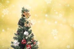 Árvore de Natal com decoração e floco de neve no bokeh do ouro Fotos de Stock