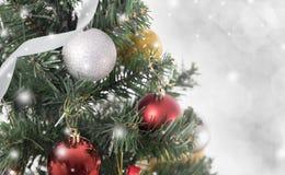 Árvore de Natal com decorações e floco de neve no bokeh Fotos de Stock