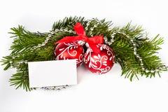 Árvore de Natal com esferas e o cartão vermelhos Fotografia de Stock Royalty Free