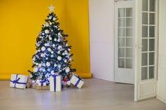 A árvore de Natal com presentes, festão ilumina o ano novo Fotografia de Stock