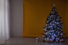 A árvore de Natal com presentes, festão ilumina o ano novo Fotos de Stock