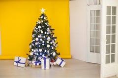 A árvore de Natal com presentes, festão ilumina o ano novo Fotografia de Stock Royalty Free