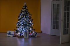 A árvore de Natal com presentes, festão ilumina o ano novo Foto de Stock