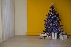 A árvore de Natal com presentes, festão ilumina o ano novo Imagem de Stock