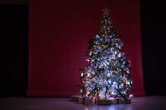 A árvore de Natal com presentes, festão ilumina o ano novo Foto de Stock Royalty Free