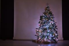 A árvore de Natal com presentes, festão ilumina o ano novo Imagens de Stock