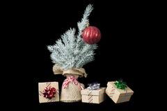 Árvore de Natal com um ornamento e presentes envolvidos na fita Fotografia de Stock Royalty Free