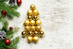 Árvore de Natal das bolas e dos ramos de árvore dourados do abeto Fotografia de Stock